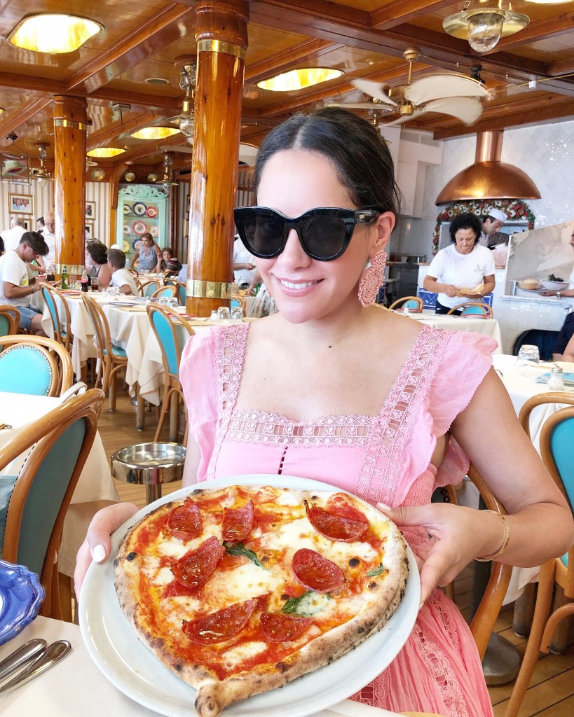 Young woman eating pizza in a cafe in Positao