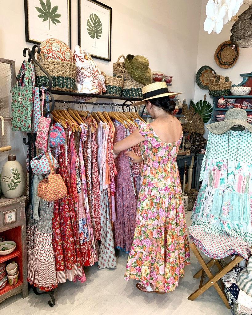 Young woman looking at beautiful clothes in a shop in Positano Italy