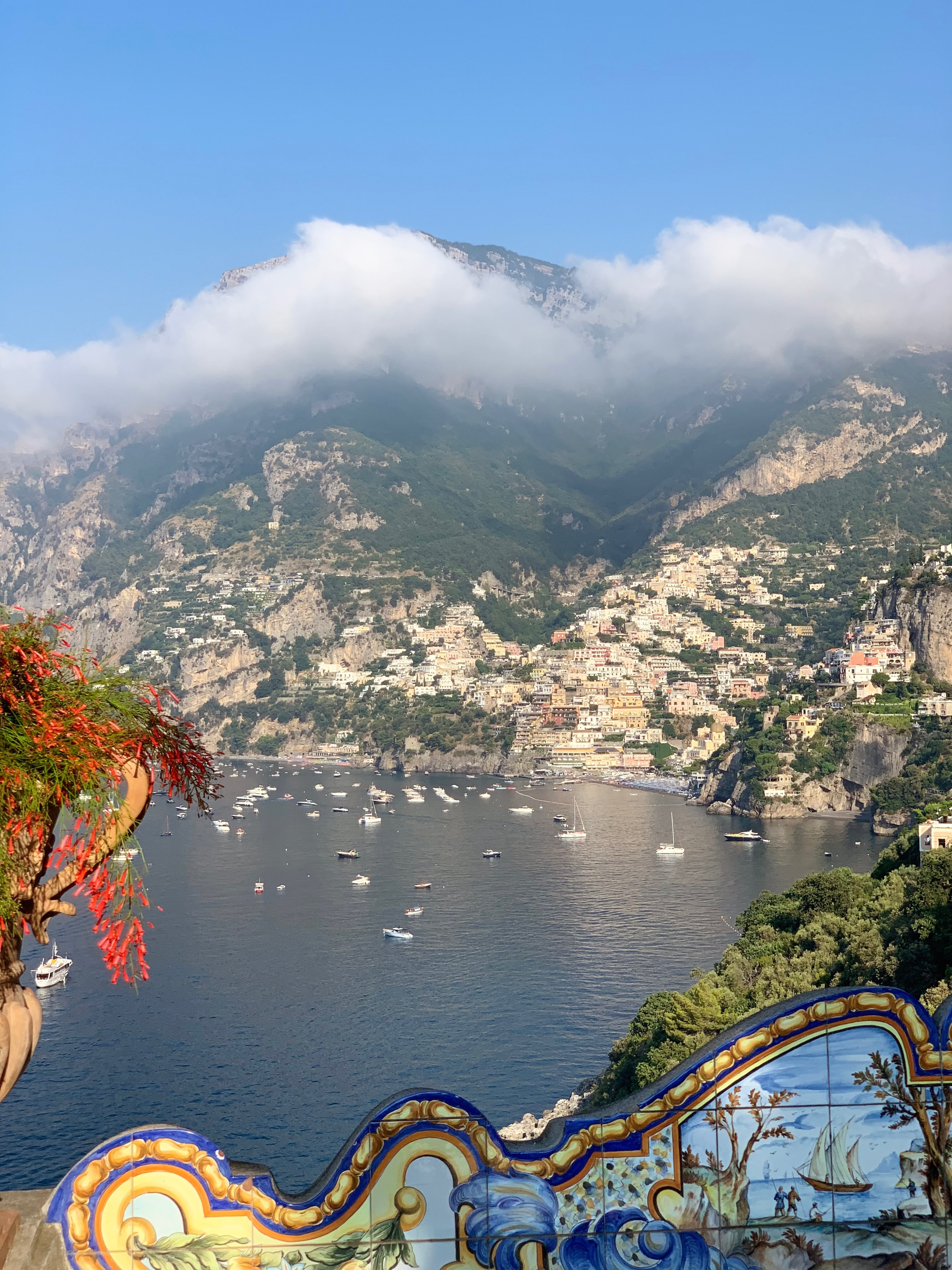 view of Positano with ships in harbor and mountainside village